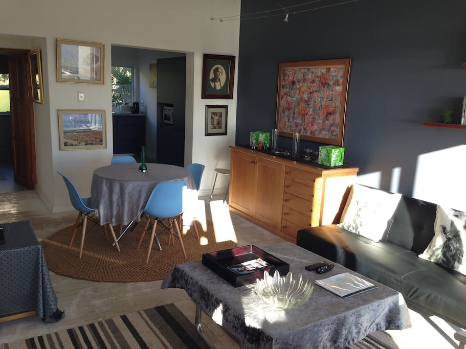 Open plan lounge dining area onto kitchen with lots of art