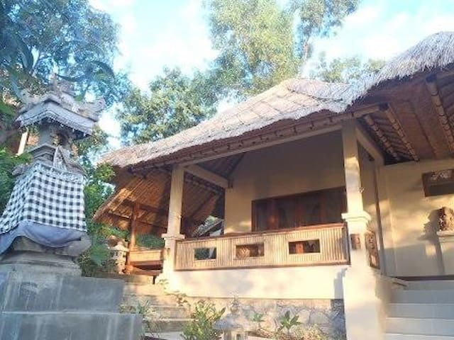 Front view of the Faery Garden Cottage at Om Shanti property; spacious veranda and day-bed