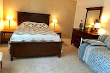 """Master Bedroom #1 is 12"""" x 17"""" It has a large queen bed and a single bed. TV, dresser and chest of drawers"""