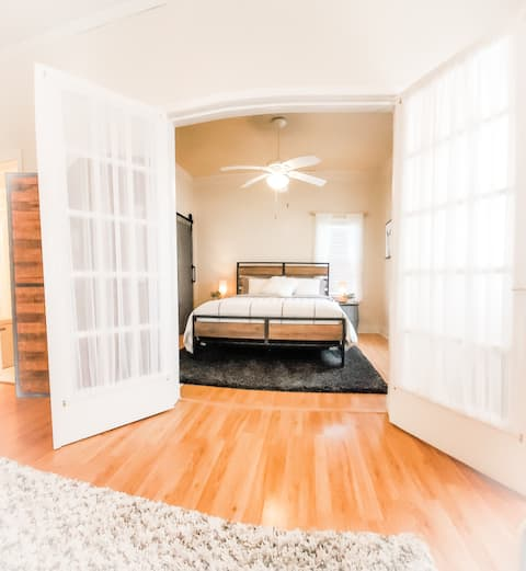 Original French doors open into the living room to reveal the master bedroom.