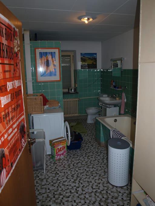 The shared bathroom with bath tub and washing machine.