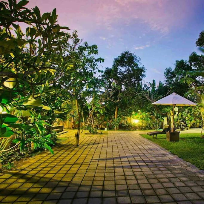 Guest house entrance with parking facilities and lush greenery