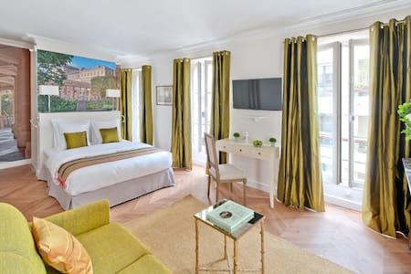 La chambre Palais Royal ouvre avec 4 fenêtres sur un passage privé arboré