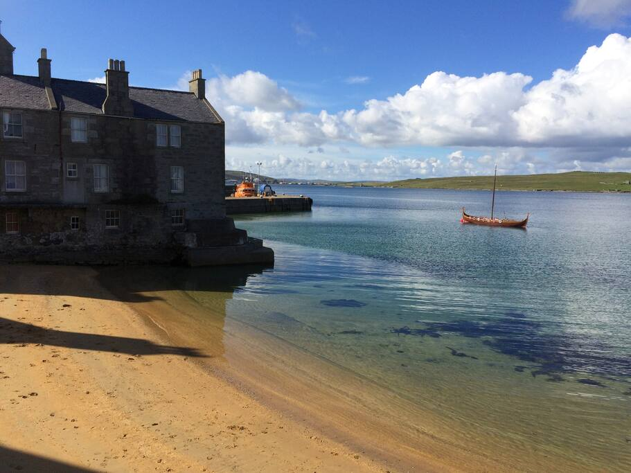 Bain's Beach, looking towards Queens Hotel and the small pier, Lerwick. The replica viking long ship, Dim Riv is anchored in the harbour during  summer months and weather permitting, you can book a harbour trip out in the Dim Riv.