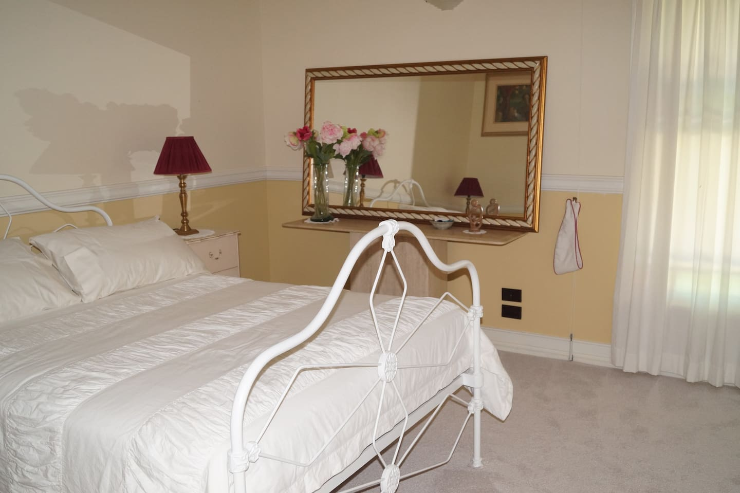 Beautiful antique cast iron double bed, quality lamps and mirror.