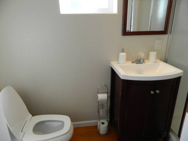 Toilet is to the left of vanity cabinets.  Please let us know if you need extra toilet paper.