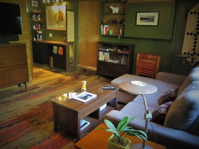 """Living area with height-adjustable coffee table, moveable  45"""" TV w/ Bluetooth sound bar, many lighting options and lots of Oregon books."""