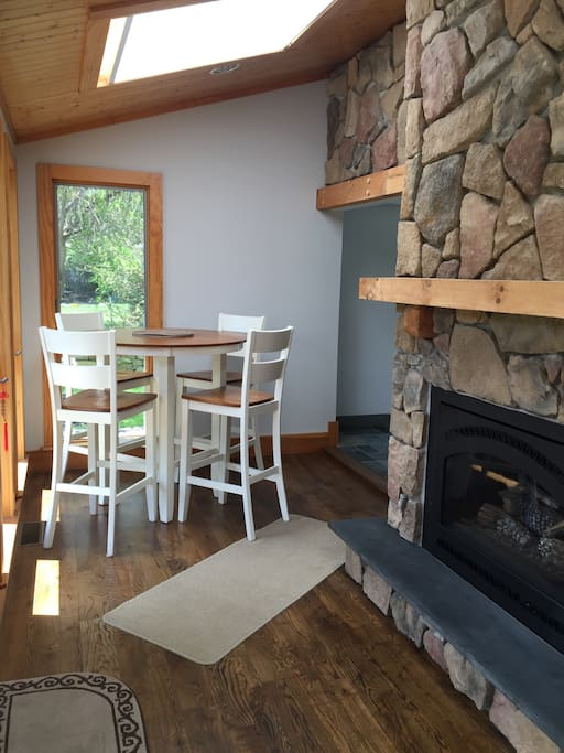 Small cafe table on porch with small gas fireplace.Views of the land trust field
