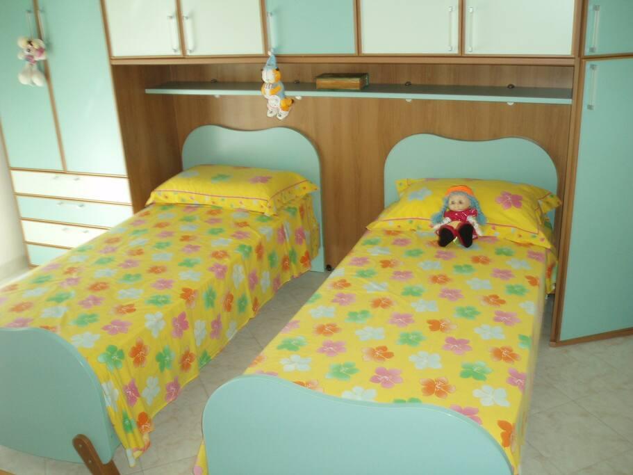 cameretta con due letti, climatizzatore, scrivanie, grende armadio e balcone