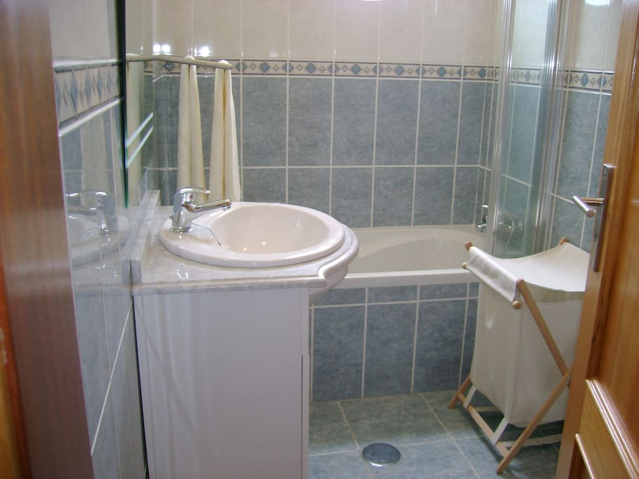 The bathroom with bath and shower.