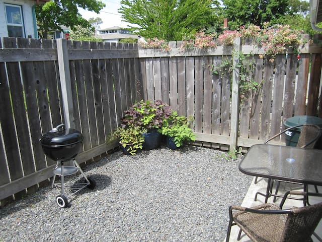 Fenced Courtyard equipped with a charcoal Weber BBQ and a patio table and chairs. A sunny spot for you to relax after a day of whale watching, hiking or shopping.
