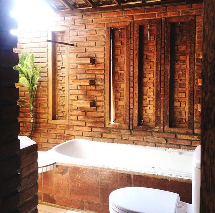 Semi-open bathroom with shower & bathtub. Hot & cold water are provided.