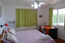 Master bedroom. WiFi router on the large desk. Seaview while sitting at the desk. Quality floor tiling. Reading lamps at the bed. Desk lamp on bedside table as well as on the desk. Aircon with remote control.
