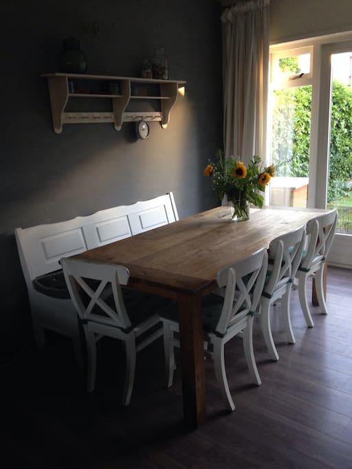 Eettafel met klapbank en 5 stoelen. Naast de openslaande tuindeuren...