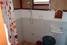 There is a toilet bowl with a flash tank, a sink and a shower. The water comes from a tank so there are no shortages and it is warmer than running water.