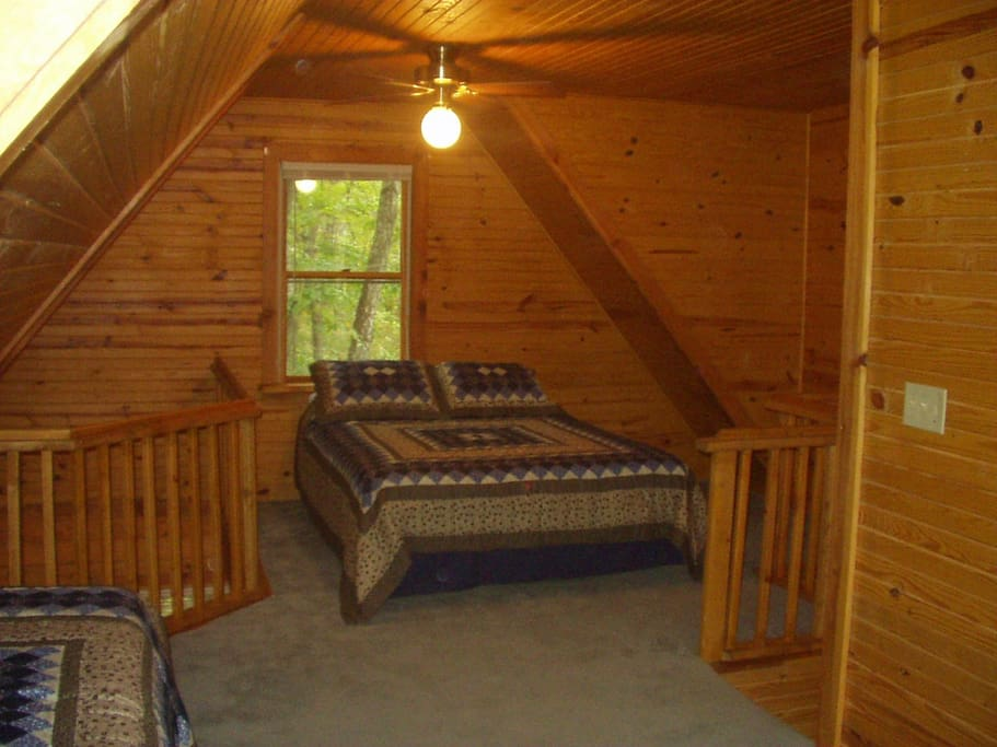 Upstairs loft - open balcony to the left, staircase to the right, twin beds, bathroom, and closet behind.