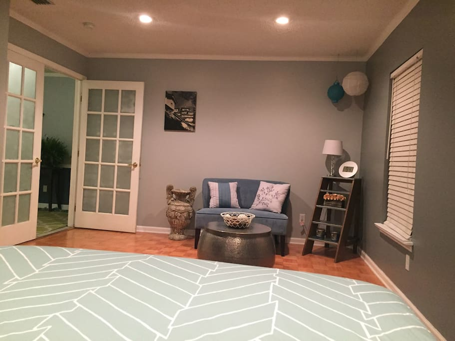 A large room with a very comfortable full sized bed, and a TV with Netflix and Amazon Prime.  The room also has a sitting area where you can relax with a good book. It even has a desk where you can get work done and a convenient outlet to plug your laptop or device into.