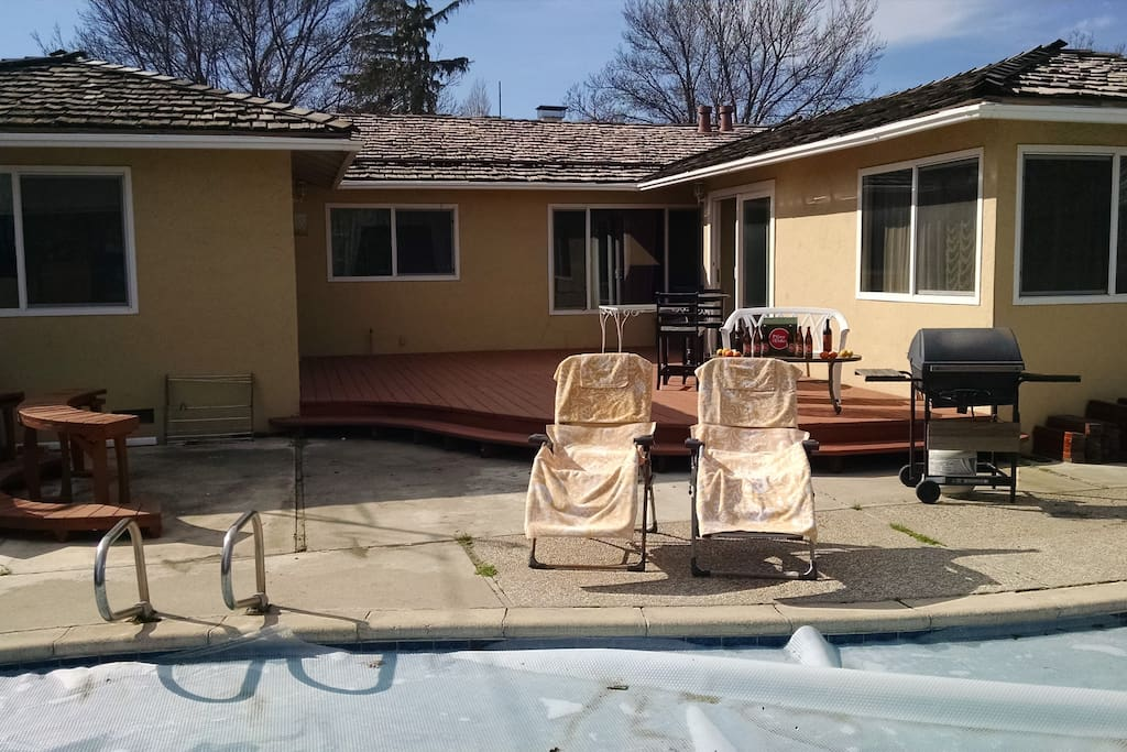 Backyard pool, large deck, barbeque, and lounge chairs