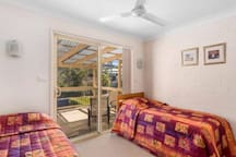 Large second bedroom with King Single Beds and large built-ins with outdoor deck overlooking pool