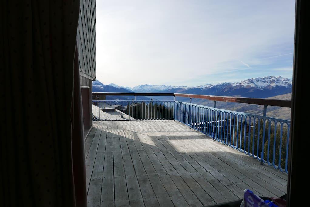 Vue depuis le séjour avec grande terrasse ensoleillée l'après midi
