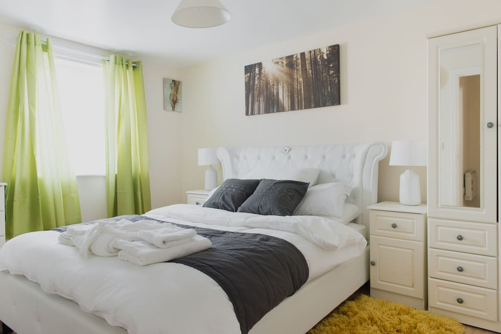Dressed kingsize bed with green therapeutic window curtains etc