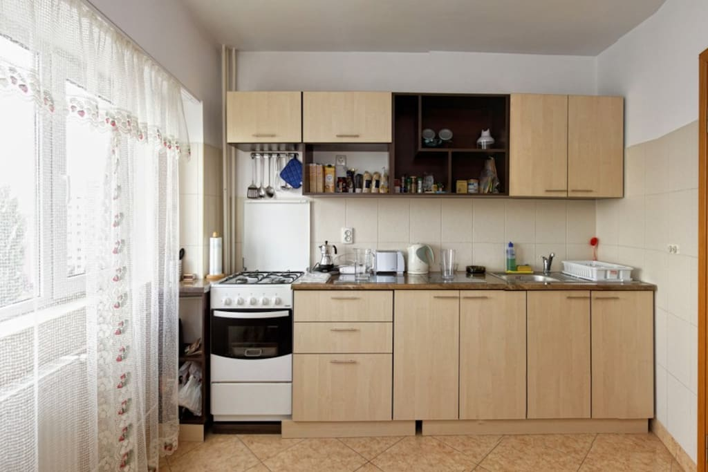 Fully equipped kitchen with appliances, such as cooking stove, hood, microwave oven, toaster, coffee maker, refrigerato