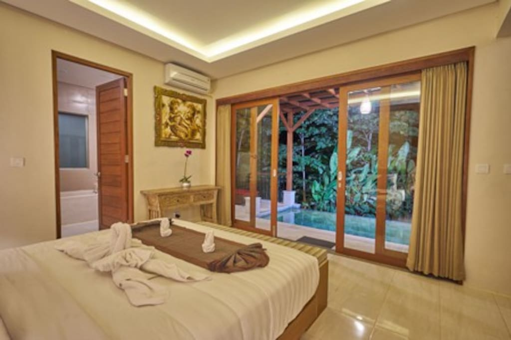 Bedroom in private villa with opening to a private pool