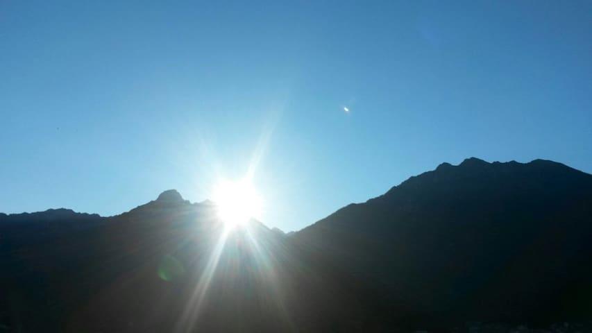 Sole che sorge dietro Pizzo Badile