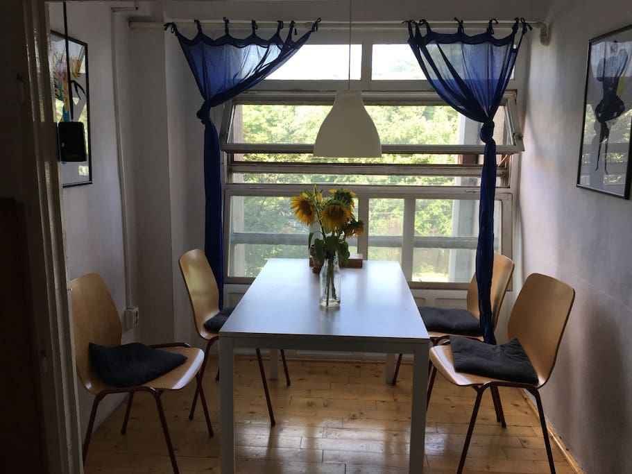 The apartment has a beautiful dining area with a large window showing the Opera house.