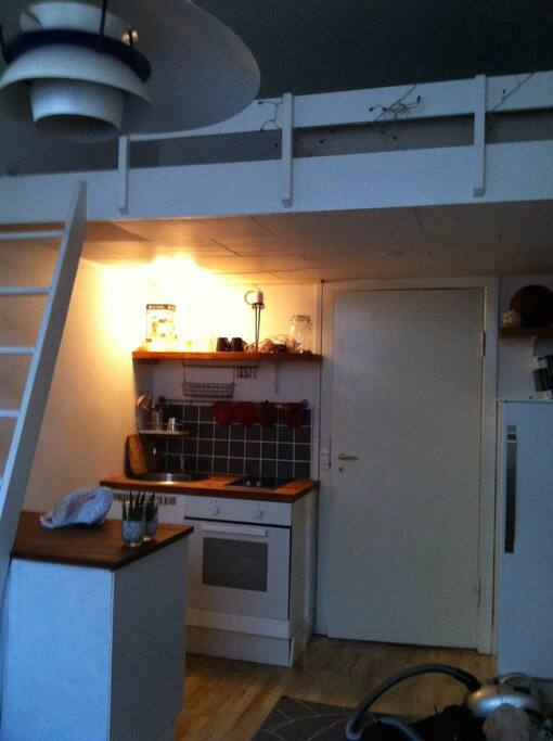 room with a small kitchen and stairs to the loft
