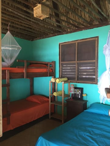Upper bedroom with one queen and a bunk, all beds have mosquito netting and each bedroom has a fan, solar night lamp, bath towels, and muebles for your personal items.