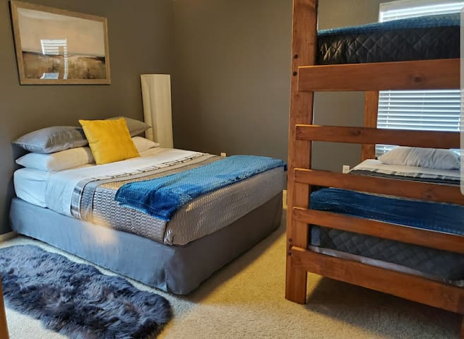Upstairs bedroom with queen size bed and a set of bunkbed.