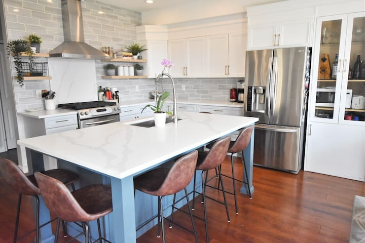 Bright open kitchen with gas stove, lots of work space and eat-in island