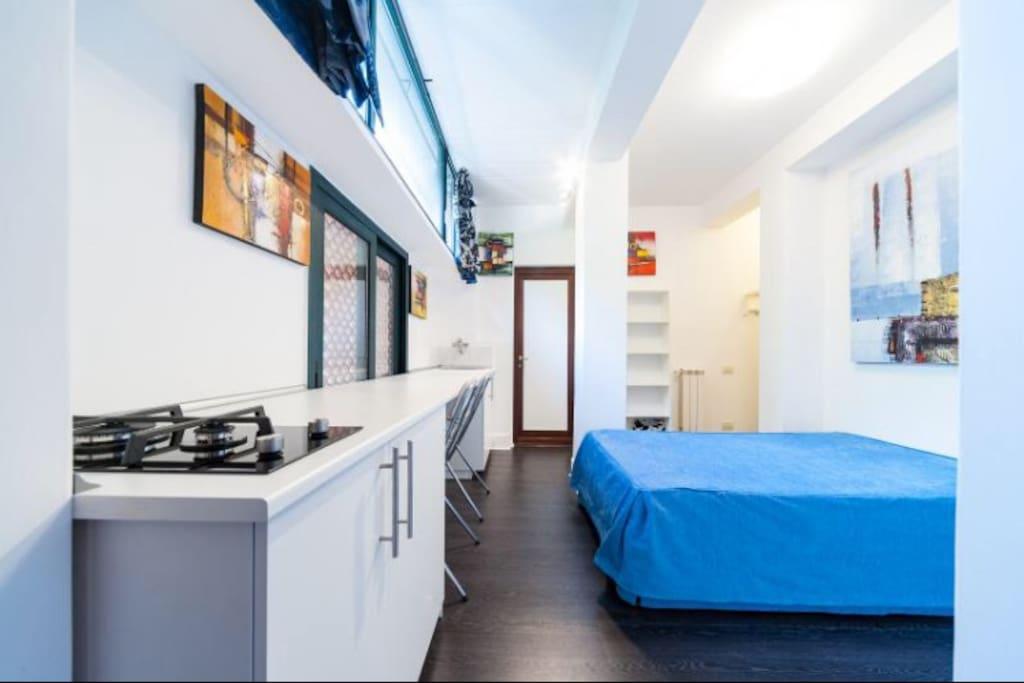 Stanza con letto e banco cucina
