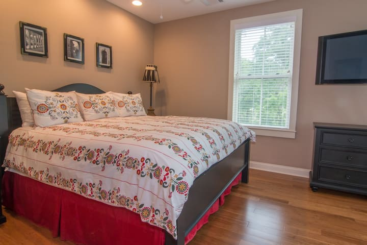 Master bedroom has a separate seating area with flat screen TV, ensuite bathroom with tub/shower, and a large walk-in closet.