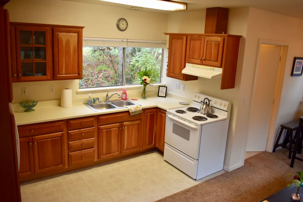 Kitchen with full size refrigerator, stove, oven, dishes & cooking needs with a foliage view