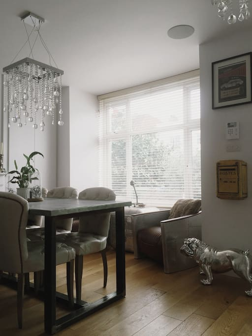 6 seater dining table and seating in bay window. View is of a small garden and the street. Open plan split by the staircase to floors above.