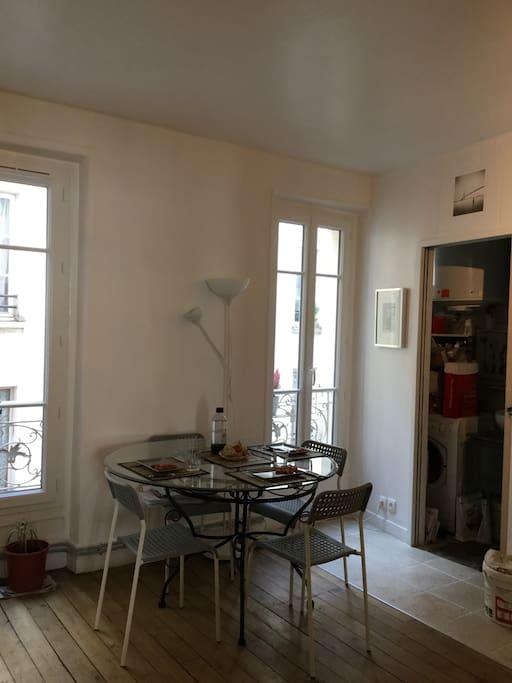piece commune: table ronde en verre + 4 chaises, deux fenêtres sur cour
