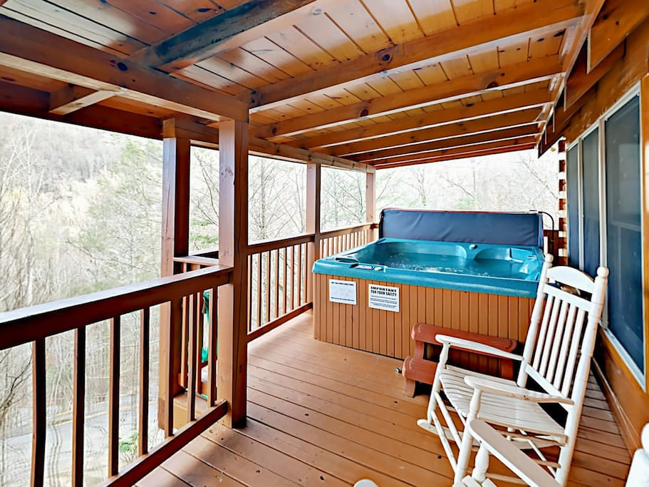 Secluded, 2-story deck with rocking chair and huge hot tub.
