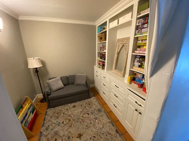 Playroom has a foldout couch and lots of puzzles, games, and books for kids and grownups