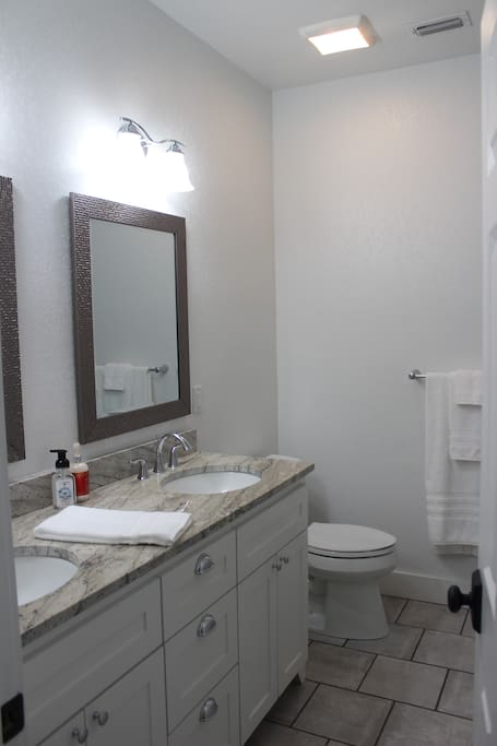 Across the hall is a shared bathroom with double sink vanity and full bath.