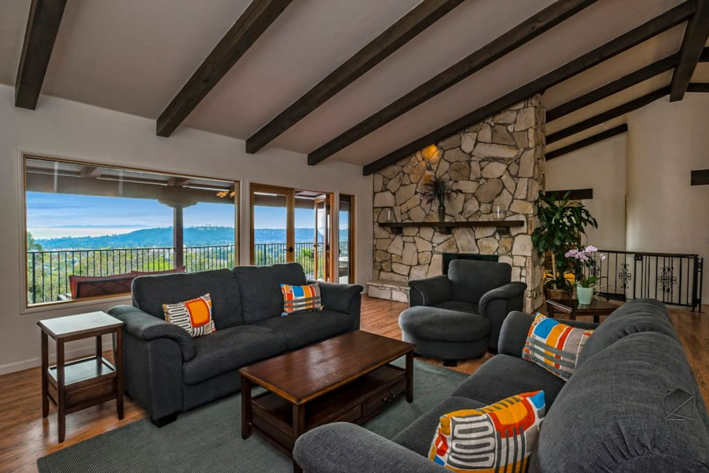 High ceilings in the living room creates a spacious atmosphere and the stone fireplace adds ambience.