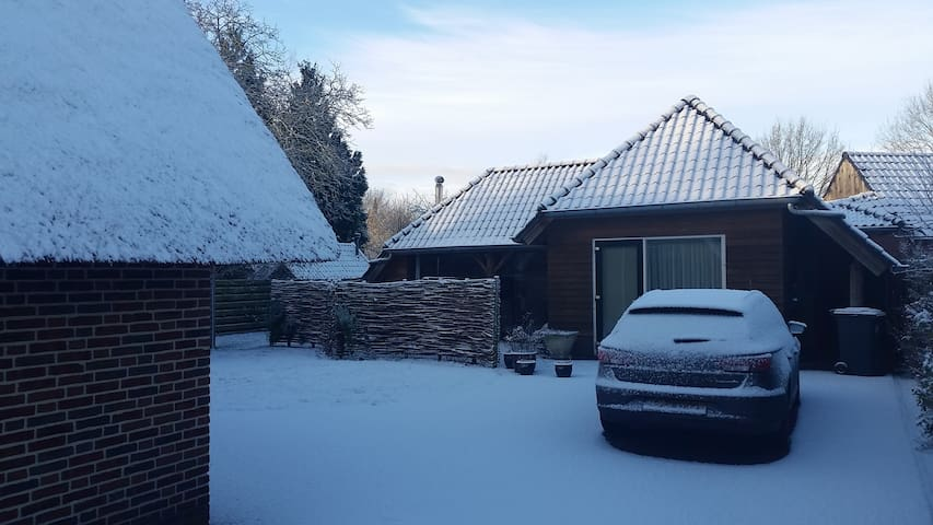 Foto in de winter van het huisje, Auto kan men voor de deur parkeren