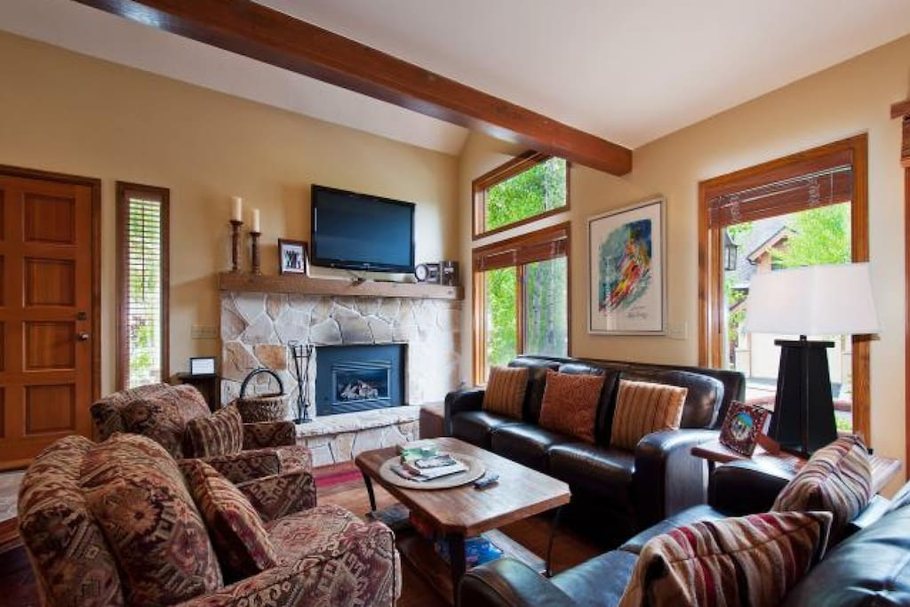 The beautiful living room has a large stone fireplace with mantle, large HDTV with Comcast TV, comfortable leather furniture and views.