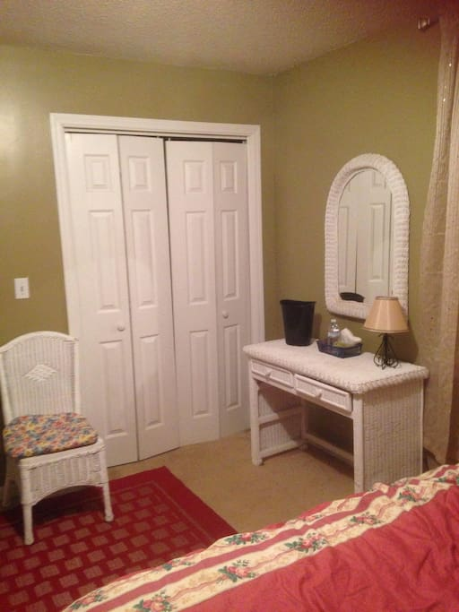 A nice little desk area with chair and a double closet with organizer shelving.