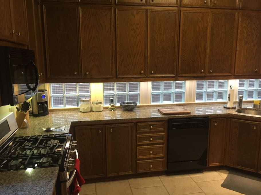 Spacious kitchen with gas-range stove, dual ovens, microwave oven, stainless steel fridge and ample counter space