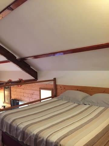 Chambre à l'étage avec un lit 140 et la télé.