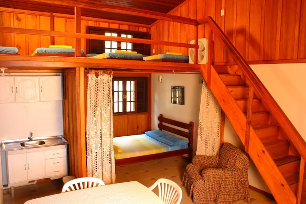 Vista da entrada (cozinha, cama de casal e escada para o mezanino)