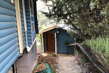 Side of the house, facing small separate cabin.