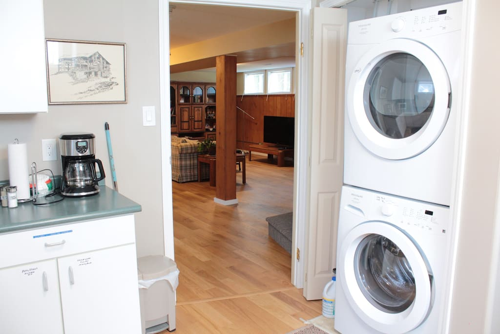 Looking through kitchen door into loving room.  Stacking washer, dryer on right.